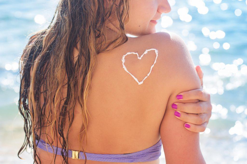 日焼け止めで背中にハートマークを描く女性